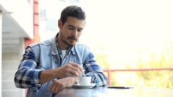 homem usando telefone celular inteligente e tomando café