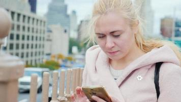 Attractive young woman in the big city. It use the phone in an urban style. New York, Manhattan, USA