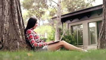 beautiful girl with a laptop sitting on the grass