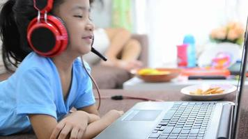 Close up shot of asian little girl using laptop computer and headphone at home video