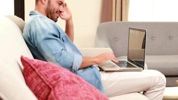 schöner Mann auf dem Sofa mit Laptop video