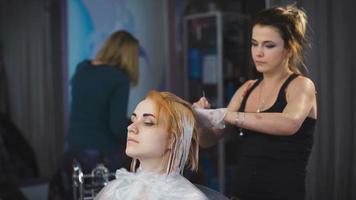 estilista cabeleireiro faz uma pintura profissional no cabelo de sua cliente