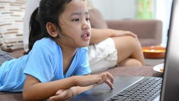 close-up de uma menina asiática usando o laptop em casa com felicidade