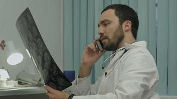 Male doctor talking on cellphone at modern hospital indoors