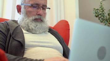 adulto sênior com uma barba grisalha trabalhando em um laptop