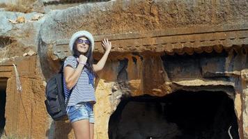giovane donna turistica che cammina vicino alle rovine. video