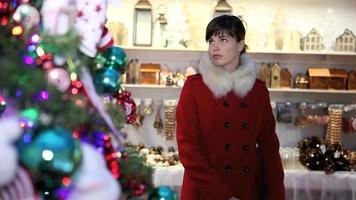Frau, die Weihnachtsdekorationen für Baum im Marktladen einkauft