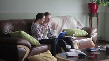 dulce pareja en el sofá con laptop saludando.
