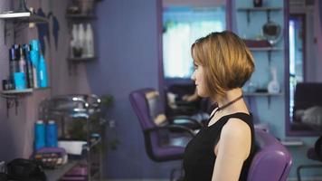 Hermosa mujer de cabello castaño en un salón de belleza aprecia su nuevo peinado