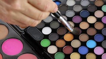 Make-up artist taking eye shadows from makeup palette video