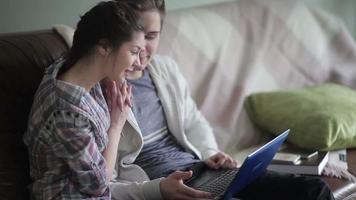 charmant couple est assis sur le canapé avec un ordinateur portable.