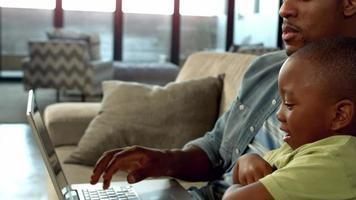 père et fils utilisant un ordinateur portable sur le canapé