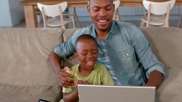 pai e filho usando laptop no sofá