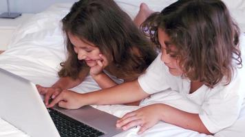 lindos hermanos usando laptop en la cama de sus padres video