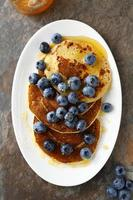 hot pancakes with berries on white plate