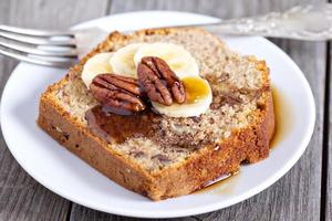 Slice of banana cake with pecans and maple syrup