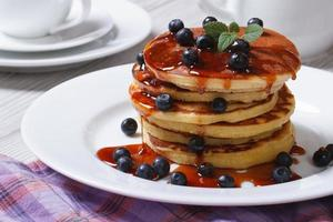 Pancake with blueberries and maple syrup on a white plate