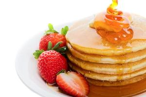 Five pancakes covered in syrup served with strawberries