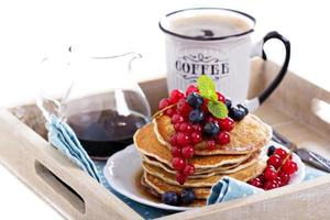 Pancakes with mixed berries isolated on white