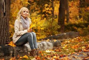 Autumn Woman. Fall. Blonde Beautiful Girl with Yellow Leaves photo