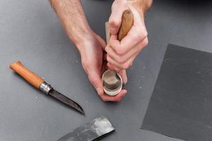 Manos de hombre tallado de una cuchara de madera con cuchillo de gancho foto