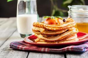 tortitas con miel, fruta y vaso de leche foto