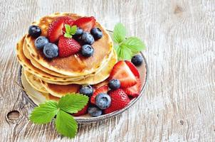 Pancakes with fresh berries  maple syrup and honey for breakfast