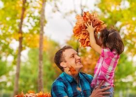 Dad and little daughter with pile of maple leaves