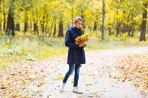 happy girl  walks in autumn park with maple leaves photo