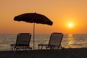 Hermosa playa con tumbonas y sombrillas al atardecer foto