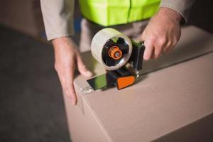 Sección intermedia del trabajador preparando mercancías para su envío. foto
