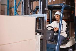 Forklift driver operating machine with boxes on it photo