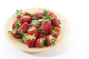 Fresh strawberries on wooden bowl photo