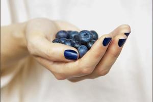 woman's hand full of blueberries