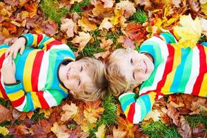 dos niños pequeños tendidos en hojas de otoño ropa colorida foto
