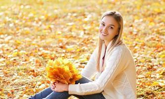 Bonita mujer sonriente con hojas de arce amarillas en otoño