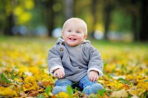 Happy little baby in the autumn park