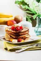 Pancakes with chocolate sauce fruit and coffee photo