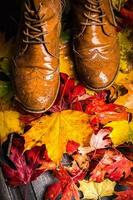 autumn leaves and old shoes on wooden terrace, fall background