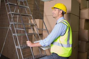 Trabajador en escalera en almacén foto
