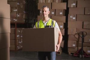 trabajador con caja en almacén foto