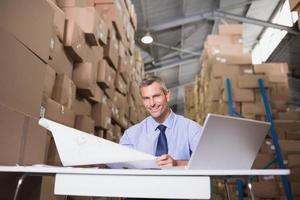 Warehouse manager with blueprint and laptop photo