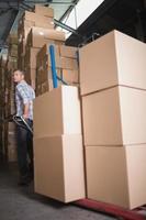 Trabajador tirando de la carretilla con cajas en el almacén foto