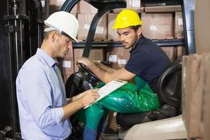 Warehouse manager talking with forklift driver photo