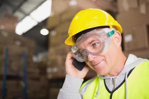 trabajador mediante teléfono móvil en el almacén foto