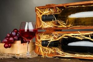 Wooden case with wine bottles, wineglass and grape