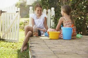 Sisters With Beach Toys Sitting In Yard