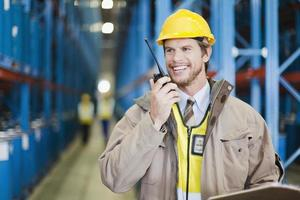 Worker using walkie talkie in warehouse