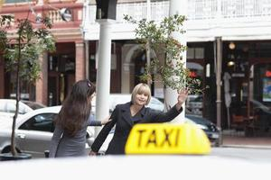 Women hailing taxi cab in city