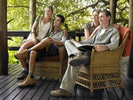 Couples Sitting In Wicker Chairs On Terrace